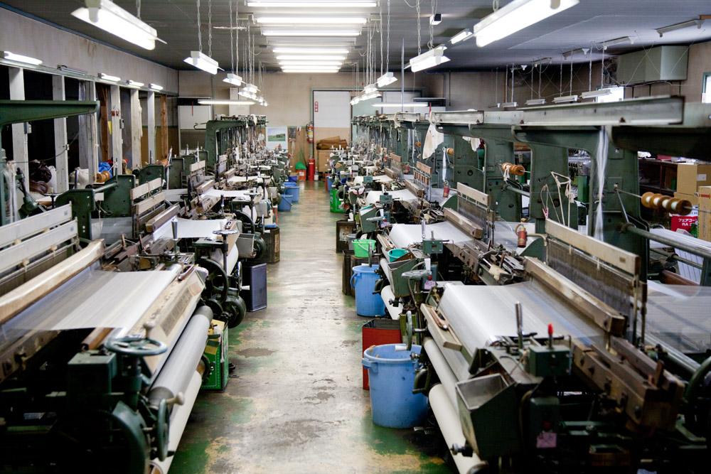 工場内部。数多に置かれた織機はどれも年期の入ったものばかりですが、ひとたび起動させるとガッシャンガッシャンと威勢良く機織りを始めます